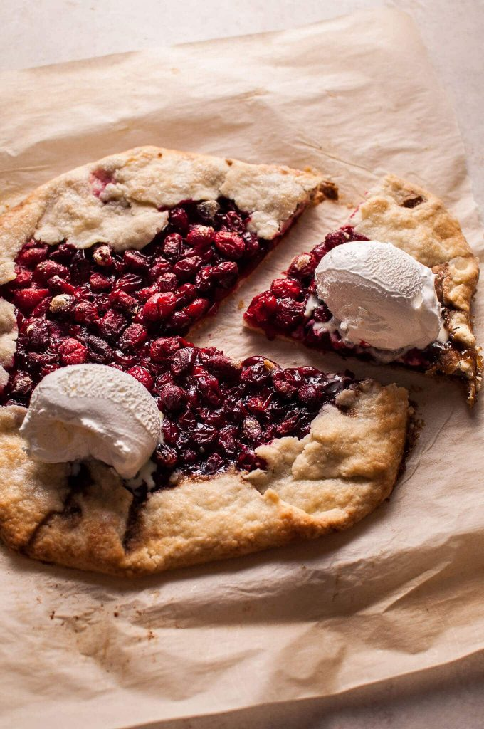 close-up of rustic cranberry galette with ice cream scoops