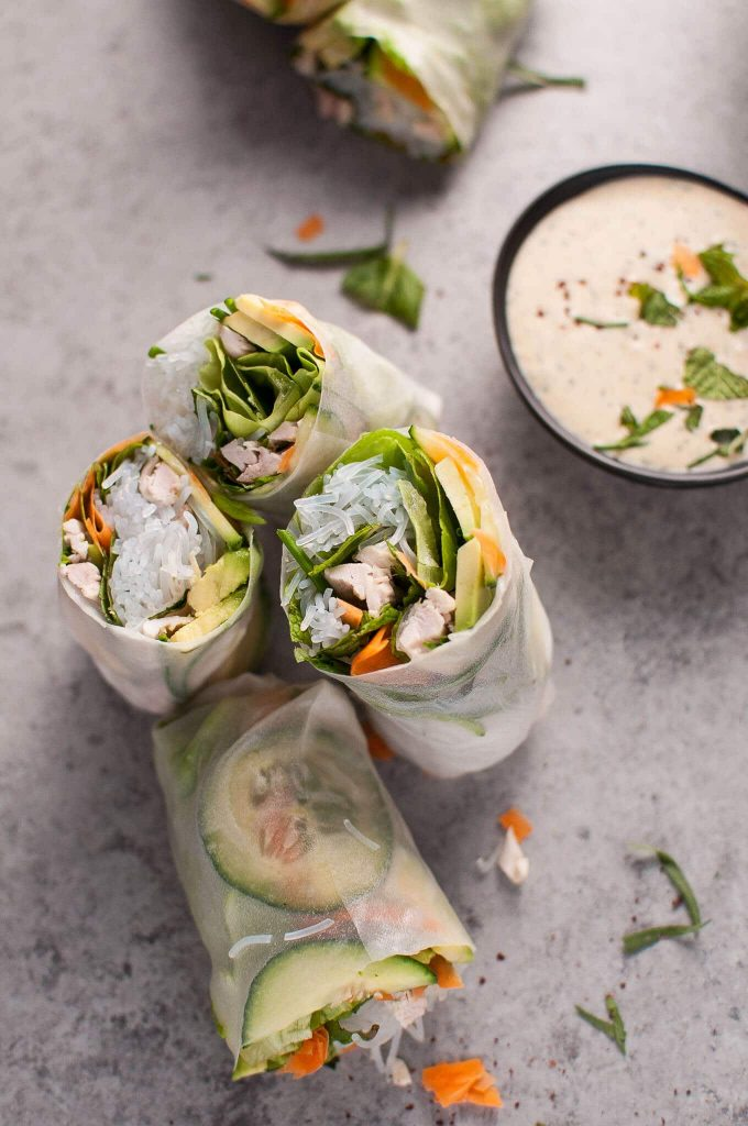 chicken salad rolls cut in half beside bowl of miso tarragon dipping sauce