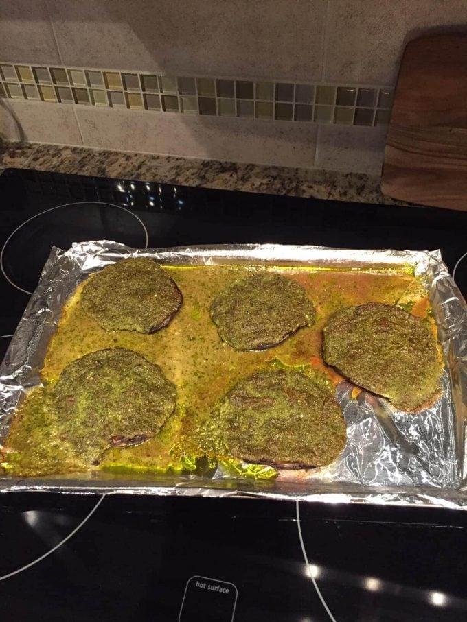 baking sheet with five pesto stuffed portobello mushrooms looking like a disaster