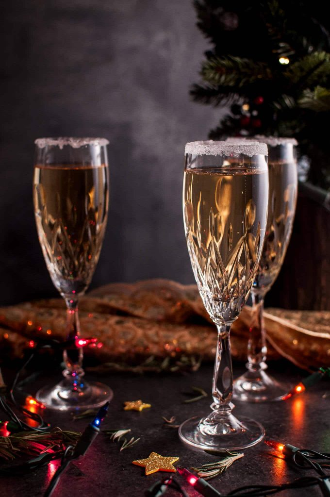 three glasses of pear champagne cocktail beside Christmas lights and tree
