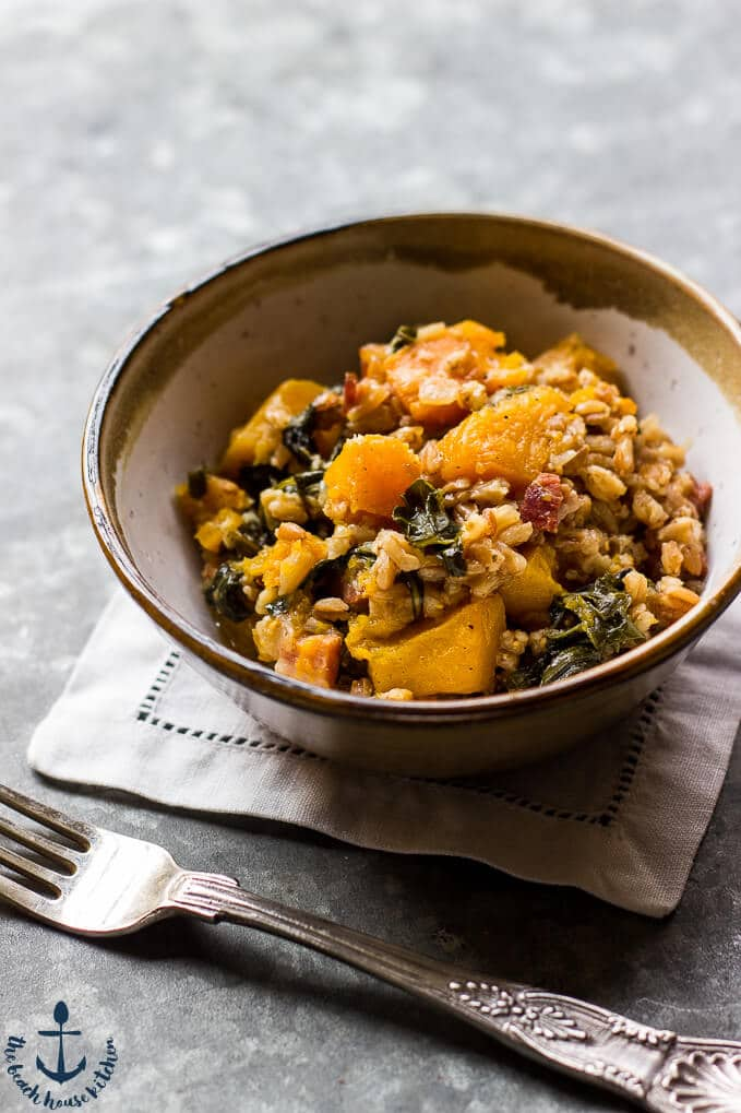 a bowl of baked farro with butternut sqaush, pancetta, and kale and a fork