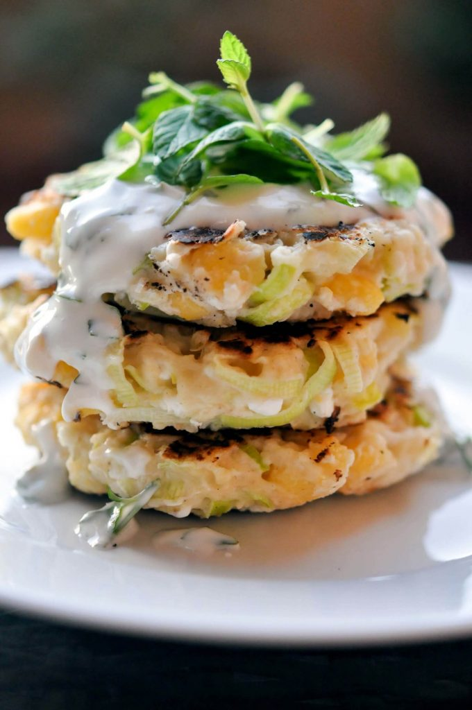 close-up of stack of three corn leek fritters with herb yogurt