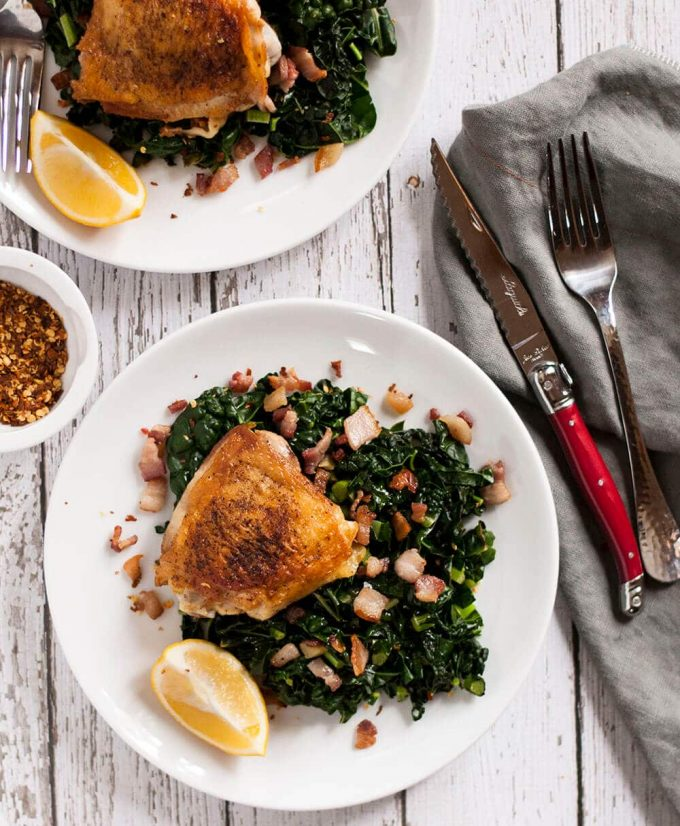 crispy chicken thighs with garlicky kale on a plate with knife and fork