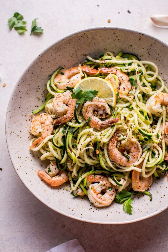 bowl with 15 minute garlic shrimp zoodles and lemon slice