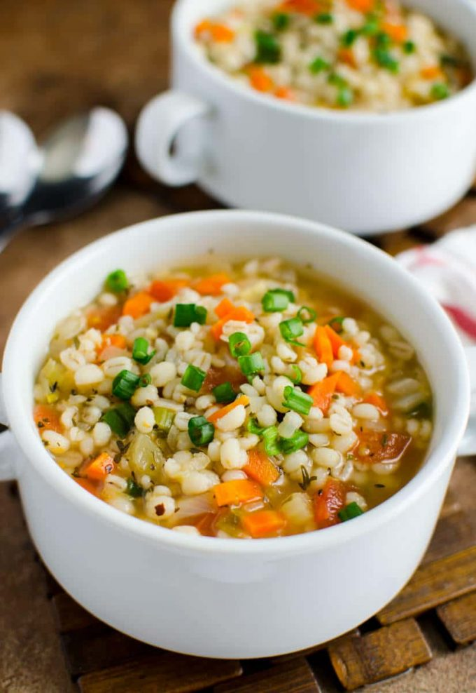 healthy barley soup with carrots in a white bowl