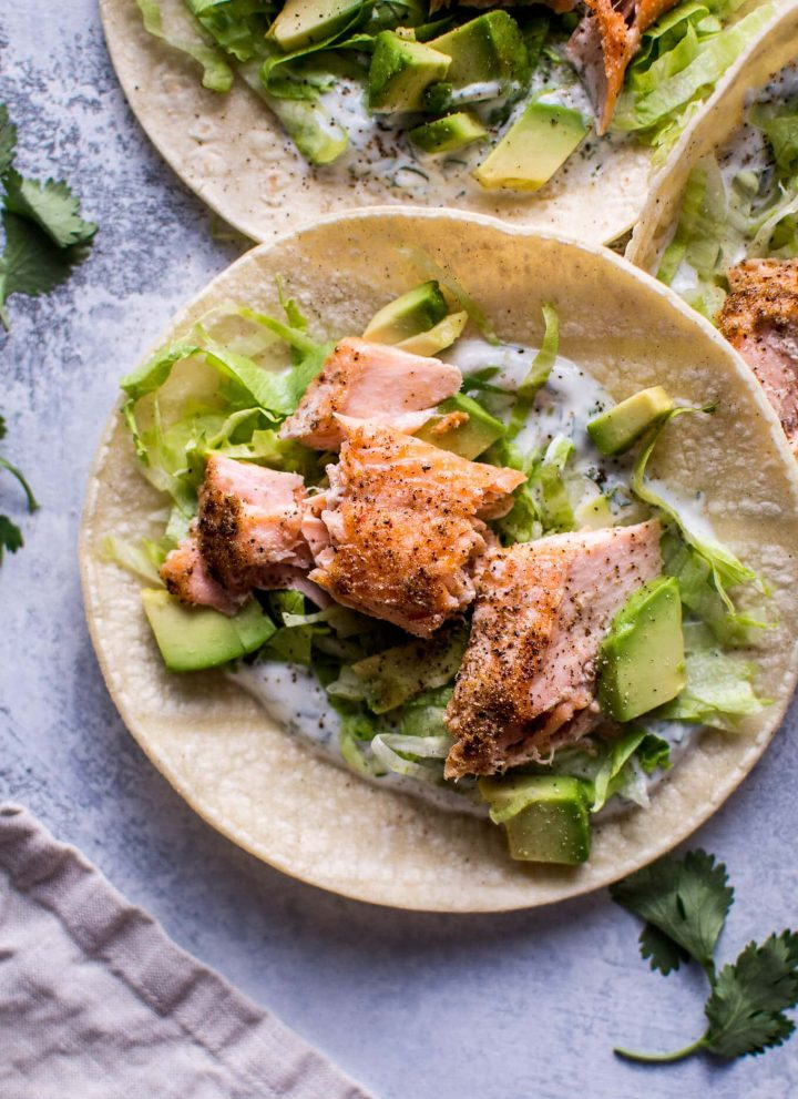 My healthy baked salmon tacos are fresh and full of flavor and ready in under 30 minutes. The cilantro lime Greek yogurt dressing tastes just as good as sour cream but contains fewer calories.