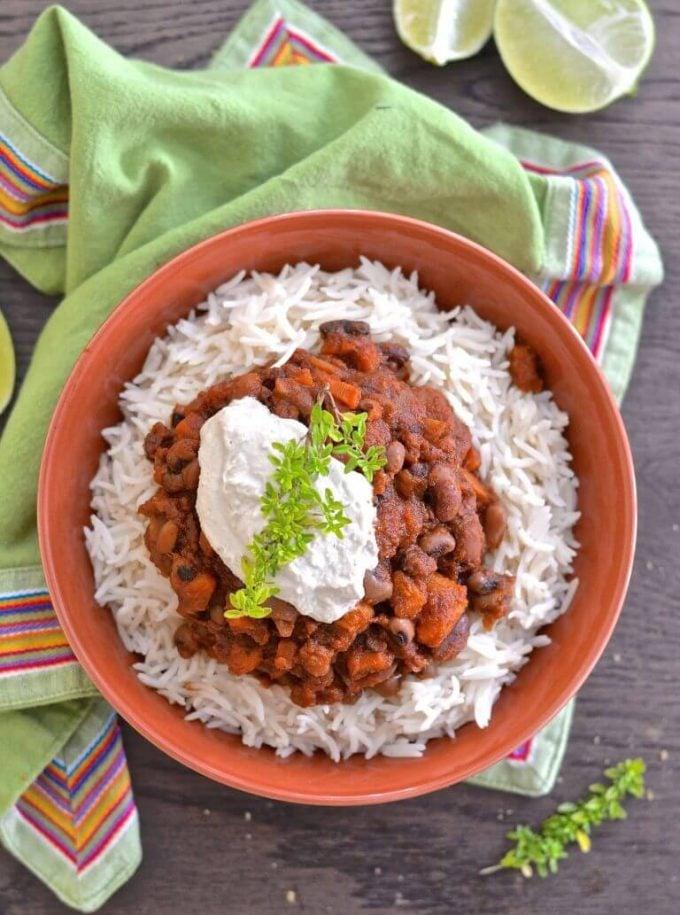 three bean sweet potato chili on rice in a bowl
