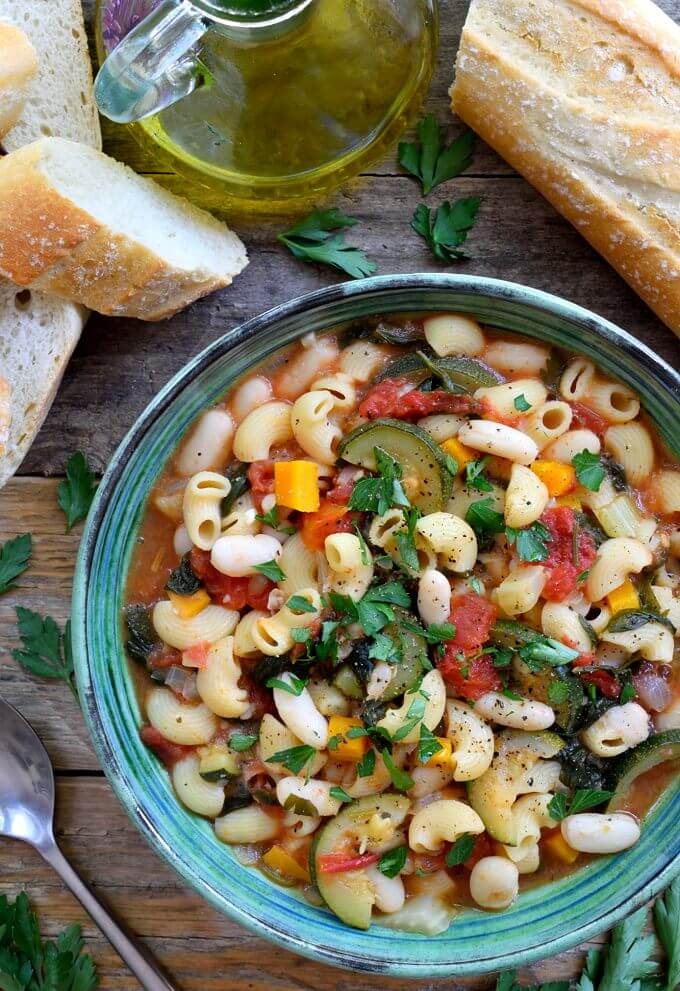 a bowl of vegetarian pasta fagioli on wooden surface with slices of bread