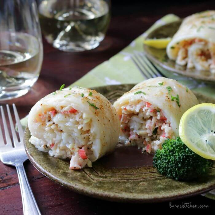 close-up of crab stuffed flounder on a plate with a fork and two wine glasses