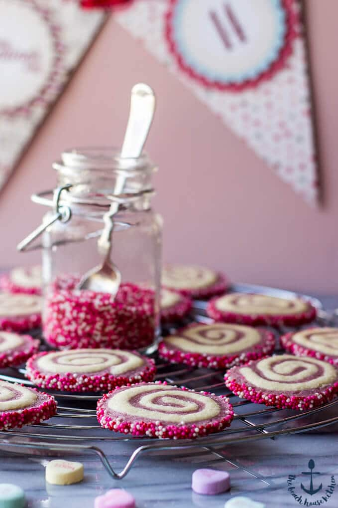 several valentine pinwheel cookies on a wire rack with jar of pink sprinkles and spoon