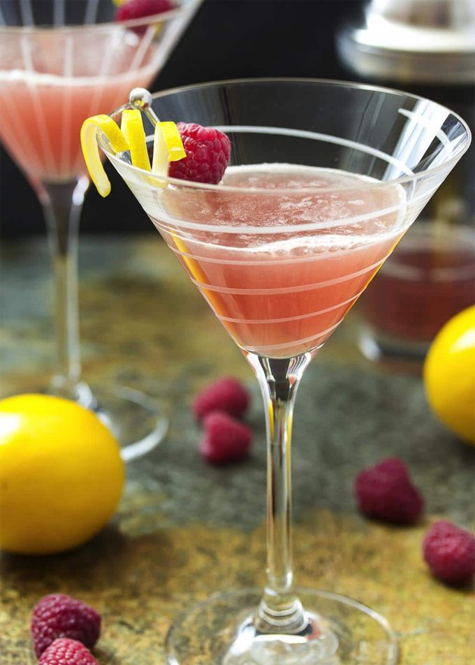 close-up of lemon drop martini in a glass garnished with lemon and a raspberry