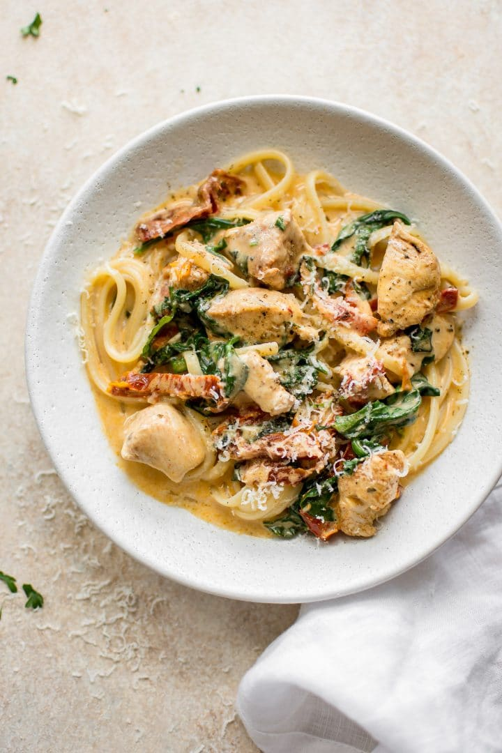 This creamy Tuscan chicken pasta recipe is even better than the Olive Garden's! You can quickly make this easy chicken, spinach, and sun-dried tomato pasta with a creamy garlic sauce at home in under half an hour!