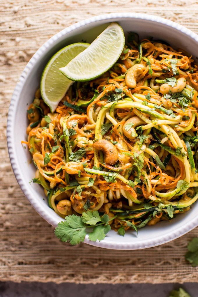 white bowl with 15 minute garlic lime cashew zoodles with lime wedges