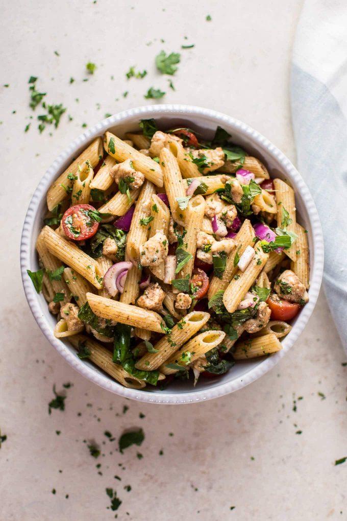 balsamic Caprese pasta salad in a white bowl beside cloth napkin