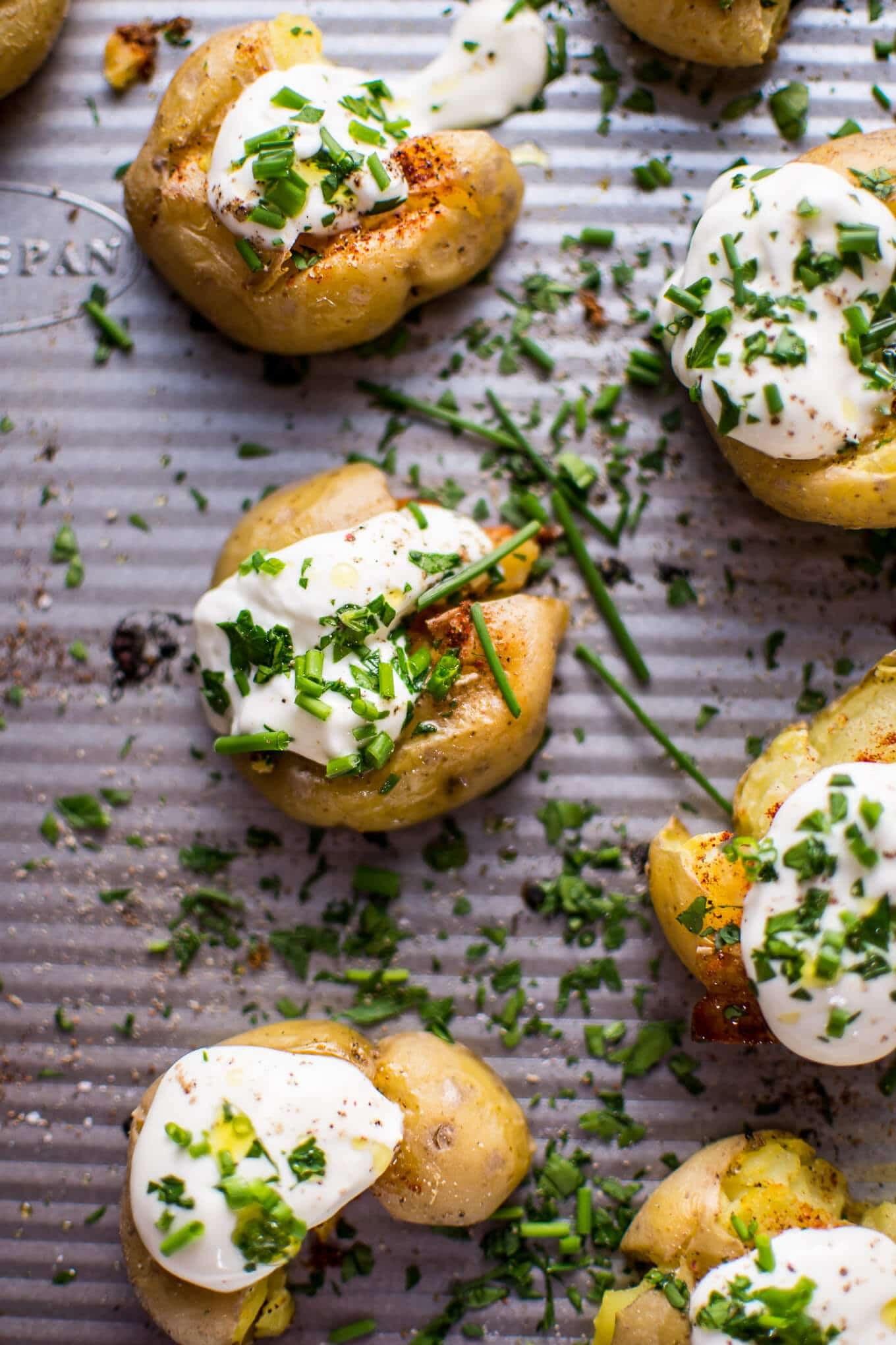 These garlic and lemon smashed potatoes are a fresh and flavorful side dish or party finger food. Replacing sour cream with Greek yogurt also makes these healthier!