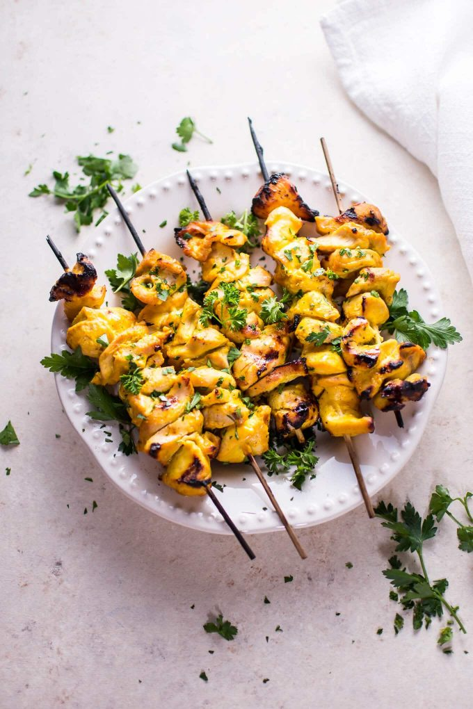 plate with five grilled honey mustard BBQ chicken skewers