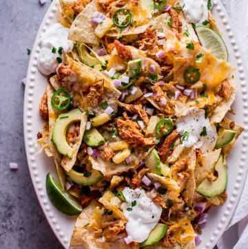 These tropical chicken nachos are a fun and tasty appetizer! Sweet and spicy chicken, pineapple, lime, avocado, sour cream, jalapenos, and lots of gooey cheese are a great combination of freshness and comfort.