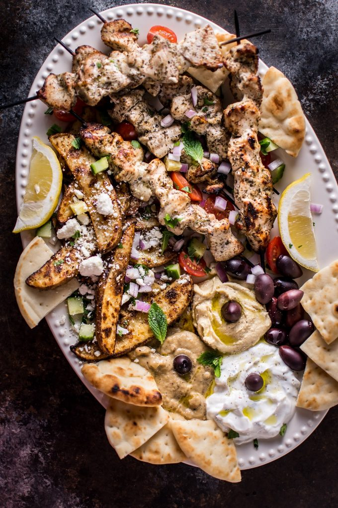 The Ultimate Greek Chicken Souvlaki Platter is loaded with tender grilled chicken skewers, pita bread, Greek potato wedges, hummus, tzatziki, melitzanosalata, kalamata olives, feta, and other goodies. The perfect meze assortment for any feast or party!