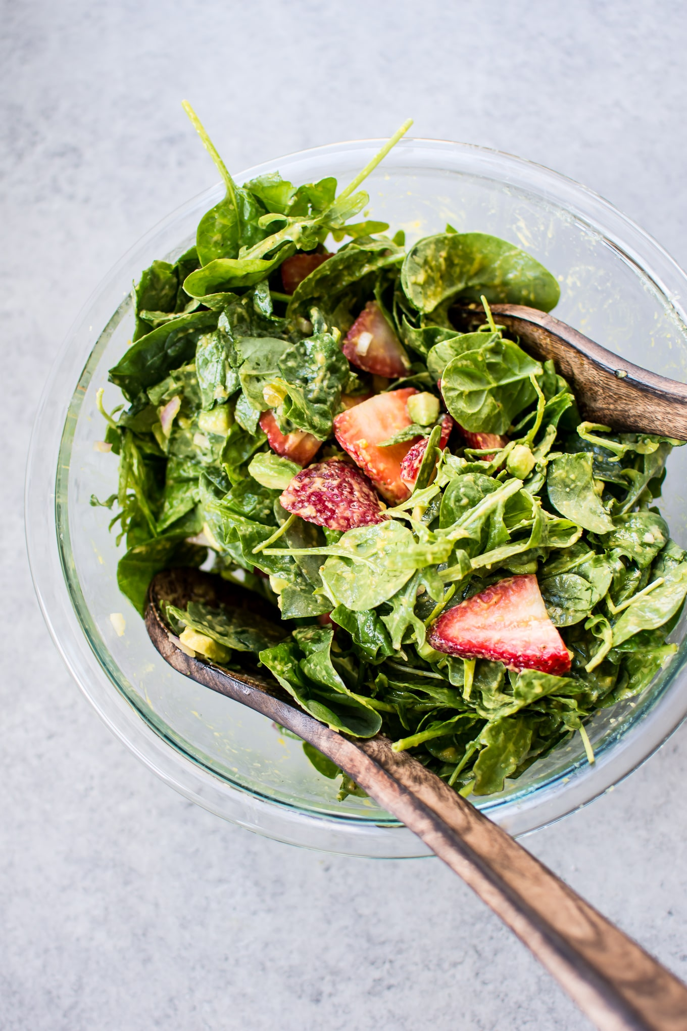 This strawberry spinach salad with mango dressing is a fresh and fruity salad that will be on repeat all summer long! Creamy avocado, peppery arugula, and red onions add a wonderful contrast to the sweet strawberries.