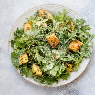This baby kale salad is an easy and fast way to enjoy kale. The lemon tahini dressing and garlicky parmesan croutons make this a wonderfully flavorful salad!