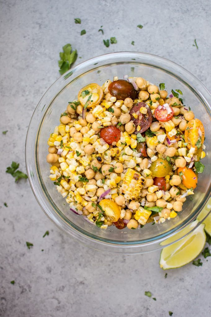 grilled corn and chickpea salad in a glass bowl with lime wedges