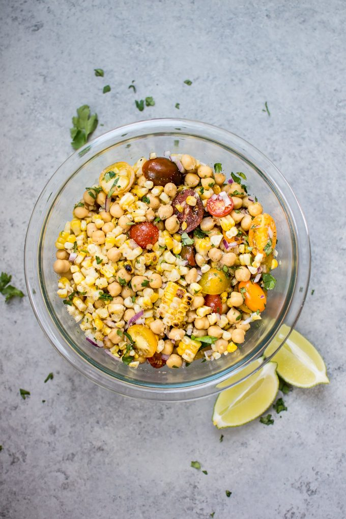 glass bowl of summer grilled corn and chickpea salad with lime wedges