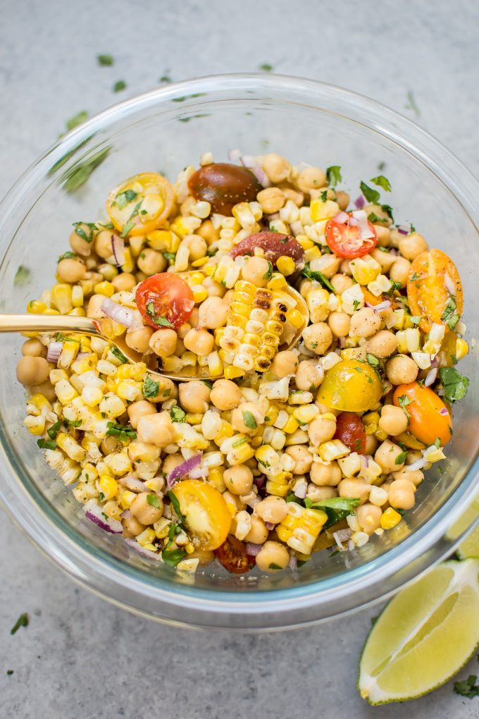 close-up of grilled corn chickpea salad in a glass bowl with a serving spoon