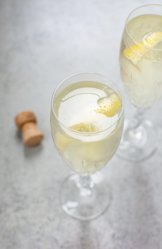 two glasses of lemon champagne cocktail beside a cork