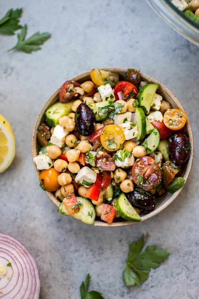 bowl of Mediterranean chickpea salad with tomatoes, cucumber, olives, and feta