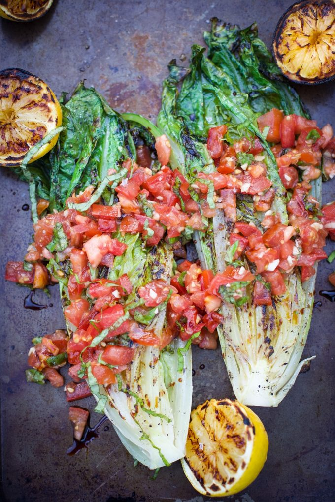 two grilled romaine lettuce heads with tomatoes and lemon