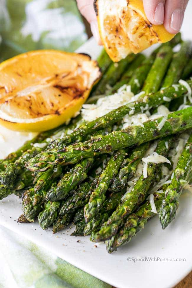 a hand squeezing lemon on a stack of grilled asparagus