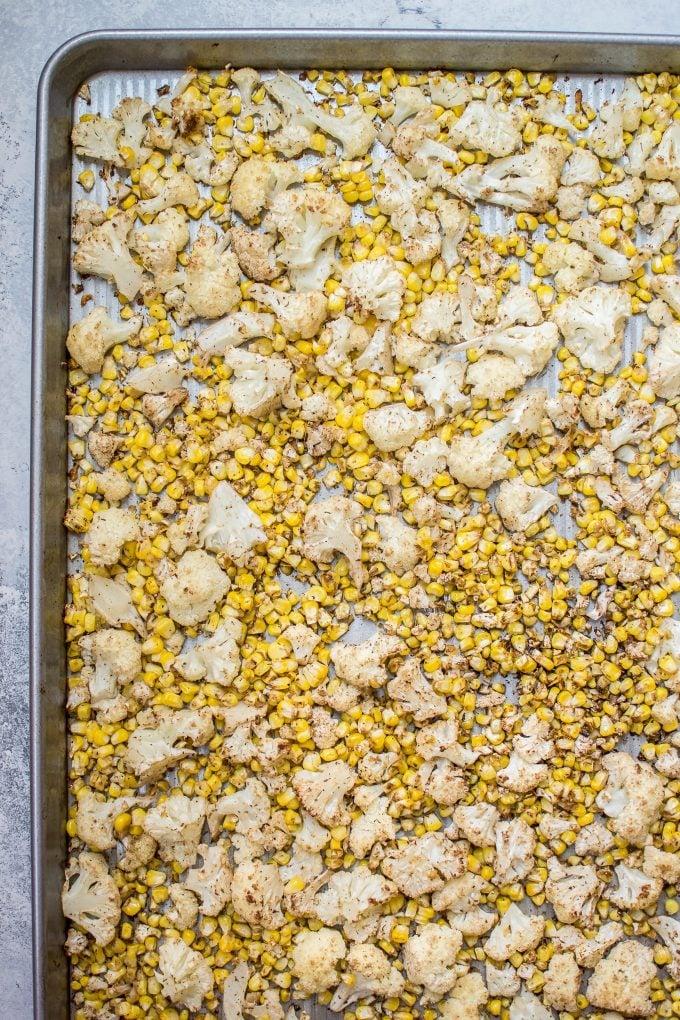 roasted corn and cauliflower on a baking sheet