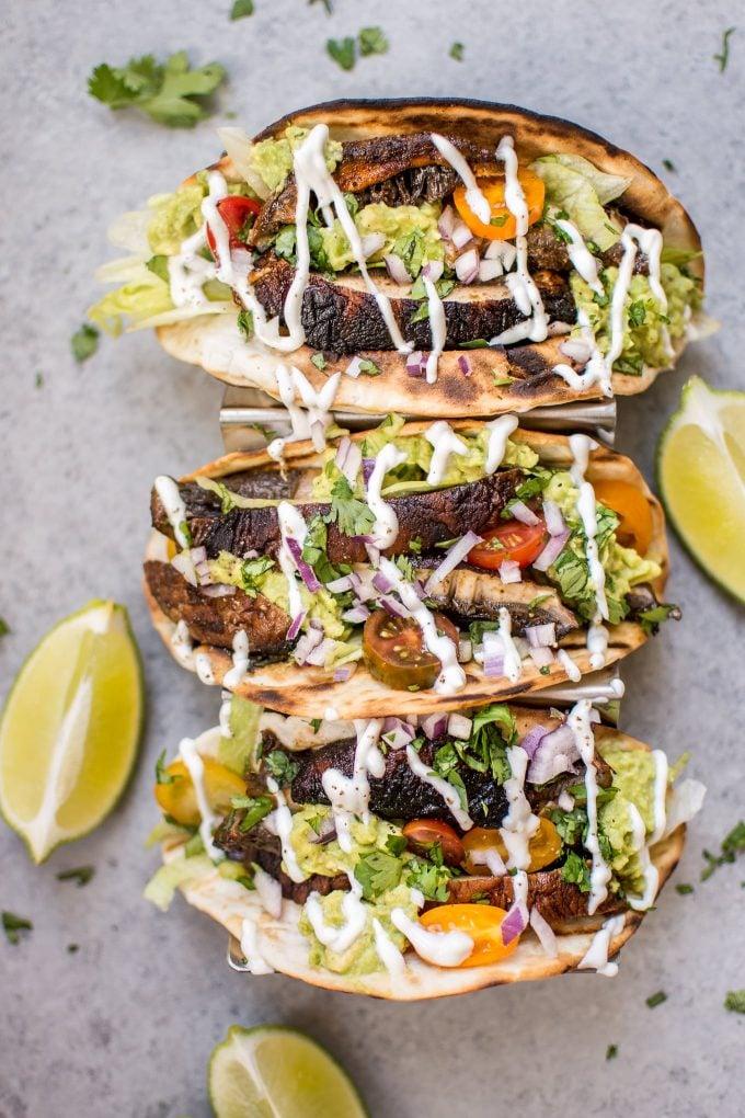 three vegetarian grilled portobello mushroom tacos beside lime wedges