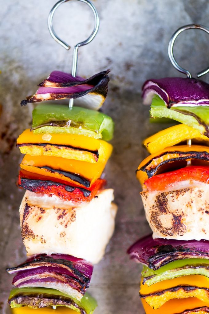 close-up of two chicken skewers with colorful vegetables