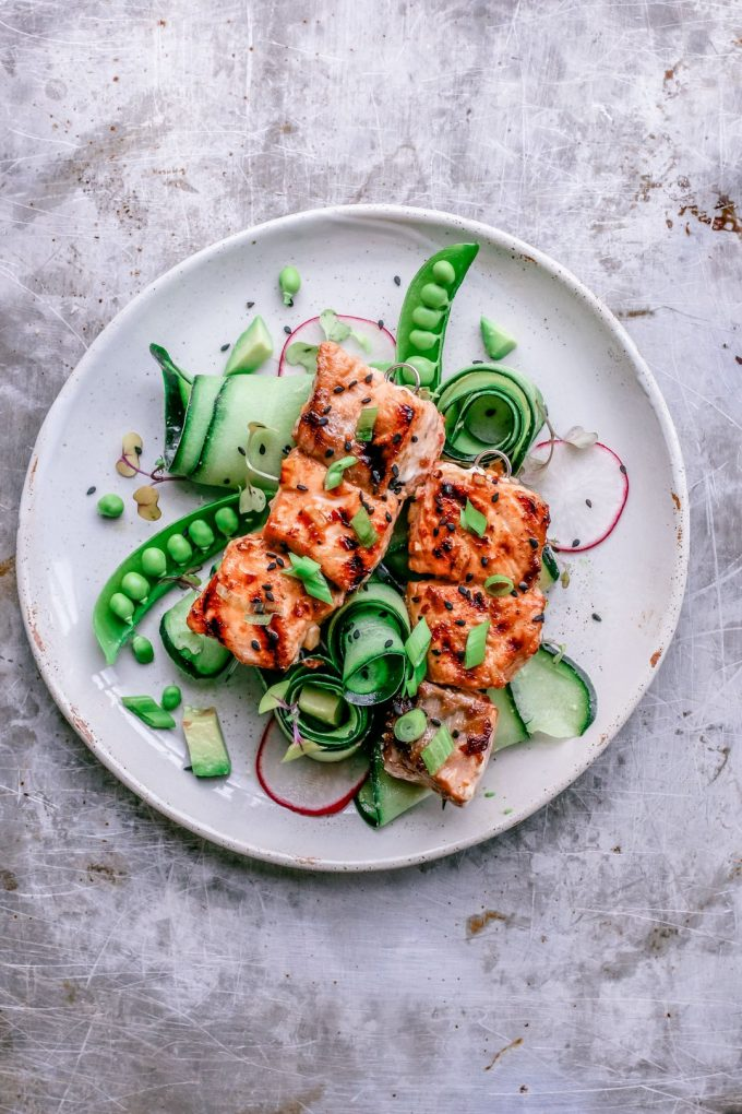 sweet chili salmon skewers on a white plate with sugar peas