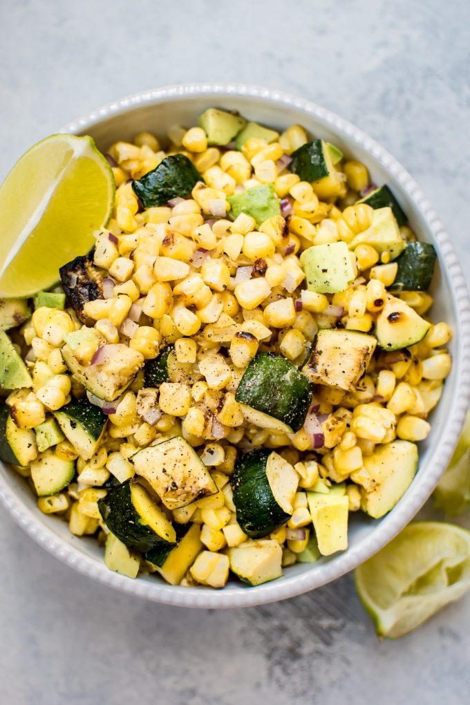 grilled corn and zucchini salad in a bowl with lime wedge
