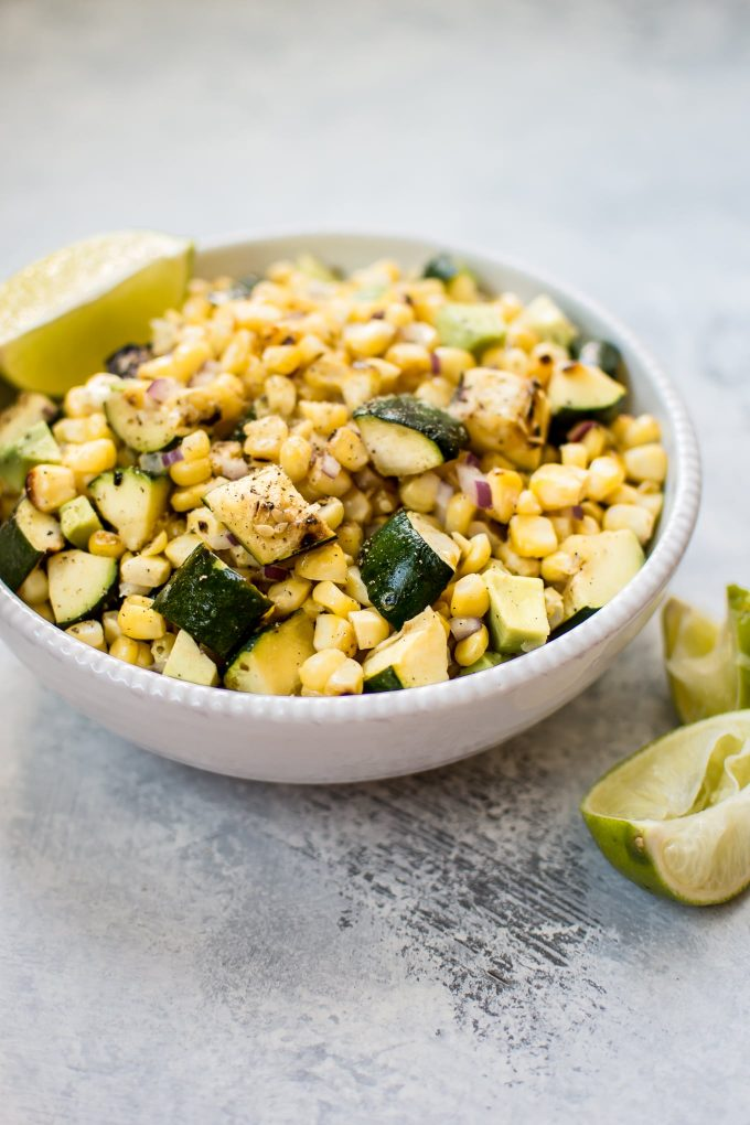 bowl of easy grilled corn and zucchini salad with lime wedges