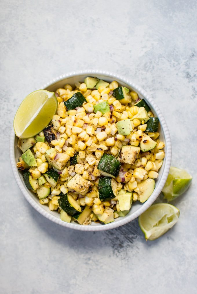 grilled corn and zucchini salad with avocado in a bowl