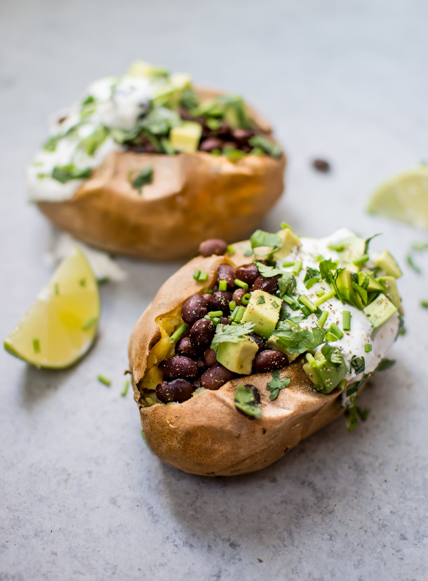 These healthy stuffed sweet potatoes make a fabulous light meal or side! Black beans with a quick lime dressing, Greek yogurt, avocado, and chives top these flavor-packed bundles of deliciousness.
