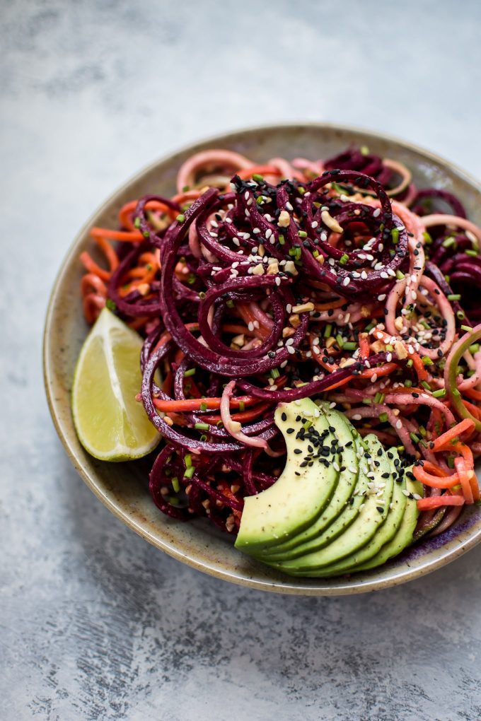 bowl of rainbow noodle salad with avocado slices