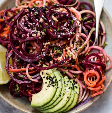 This rainbow noodle salad is a healthy, fun, and colorful dish that's made entirely of vegetable noodles. A creamy avocado-lime dressing makes it extra flavorful!