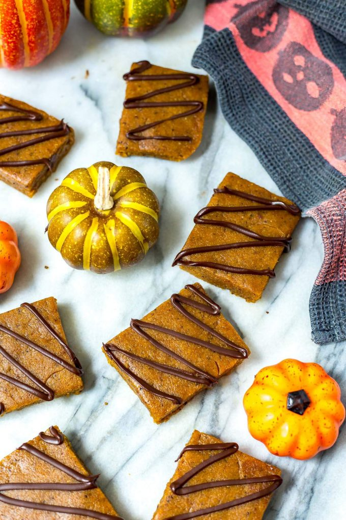 several pumpkin spice latte protein bars on a counter with mini pumpkins