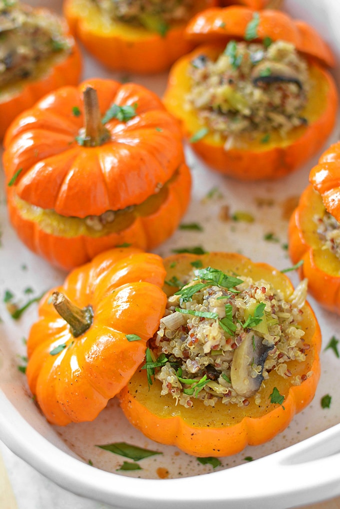 several mushroom quinoa stuffed mini pumpkins in a white casserole dish