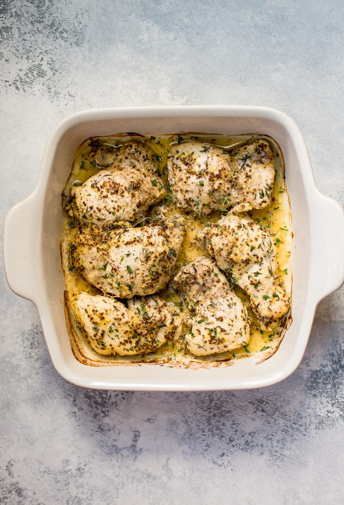 juicy roasted mustard chicken thighs in a white baking dish