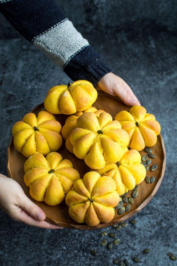 hands holding tray of several pumpkin rolls