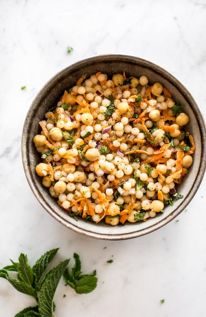 This healthy vegan pearl couscous salad has delicious fresh herbs, chickpeas, and carrots. It's the perfect light lunch or meal prep recipe.