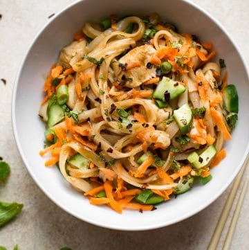 This healthy chicken stir fry with rice noodles is quick and delicious. Perfect for easy weeknight dinners! Garnished with scallions, mint, grated carrots, and cucumber.