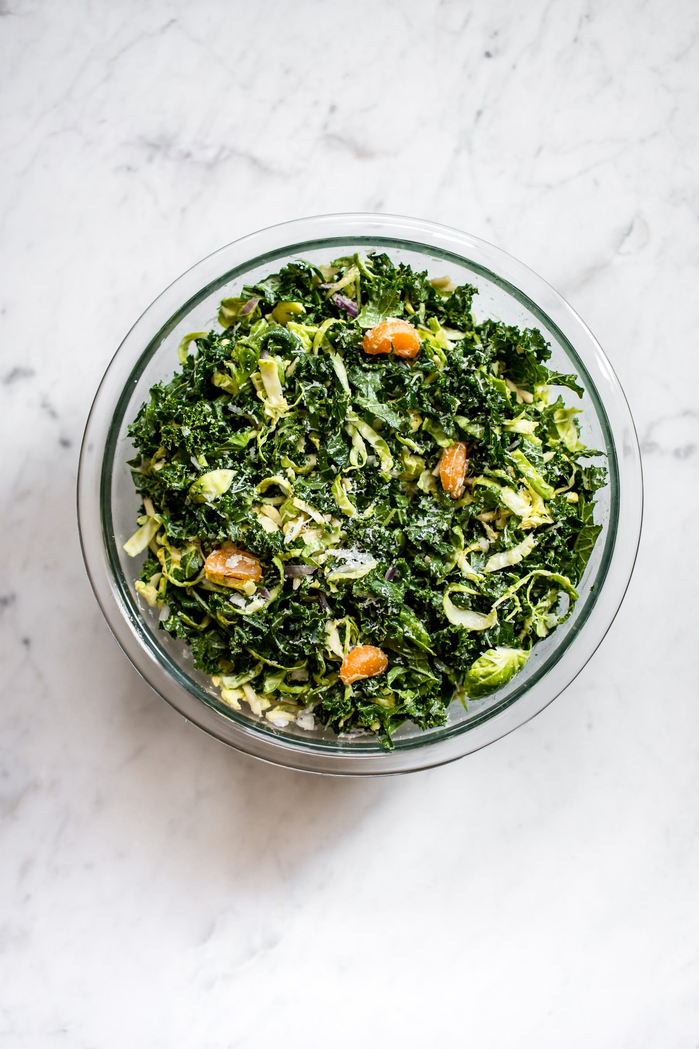 This shredded kale and Brussels sprouts salad is flavorful, filling, and delicious with pecorino cheese and mandarin oranges.