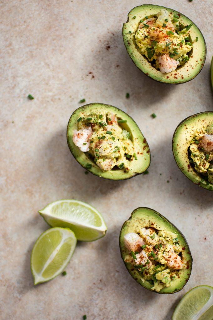 four shrimp stuffed avocado halves beside lime wedges