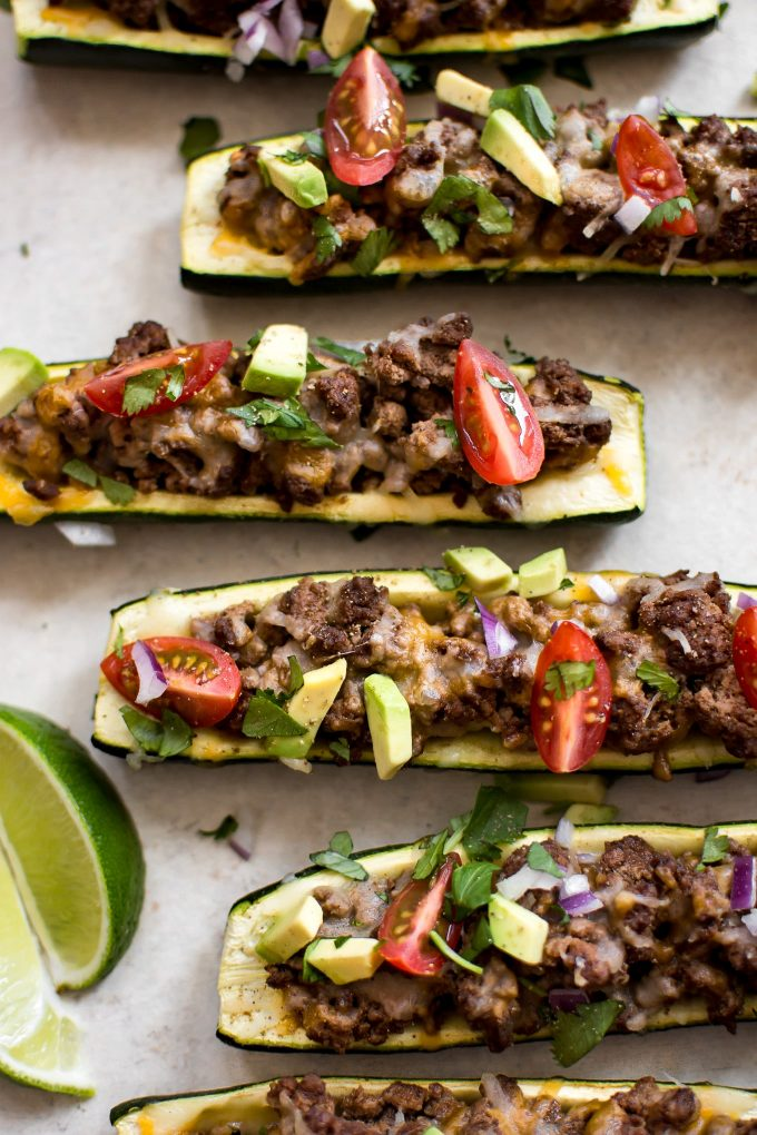 taco zucchini boats topped with ground beef, cheese, avocado, and tomatoes
